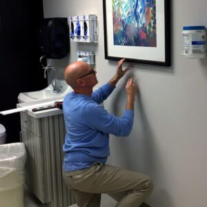 our corporate art consultants help you determine where and what to hang just as Tom is doing here